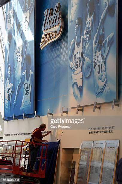 A worker installs letters on a wall from former Bruin Coach John Wooden in the renovated Pauley Pavilion on October 23 2012 Pauley Pavilion has...