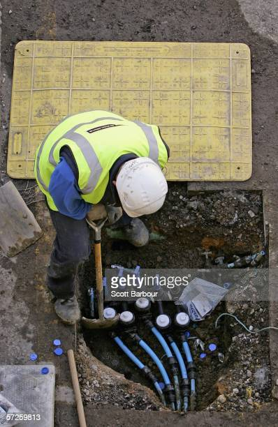 Worker installs new pipes as Thames Water begin replacing ageing water mains in a residential street on April 5, 2006 in London, England. Thames...