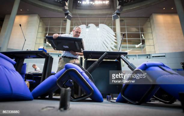 A worker installs new seats and working spaces for parliamentarians in the Bundestag at the Reichstag on October 17 2017 in Berlin Germany Following...