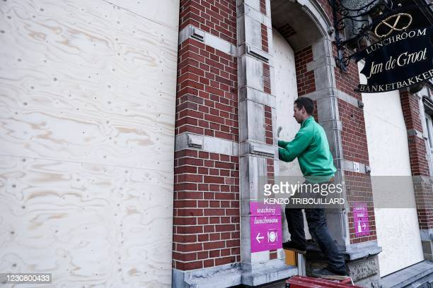 Worker installs protections on a store in the city center of Den Bosch, on January 26, 2021 a day after police clashed with groups of demonstrators...