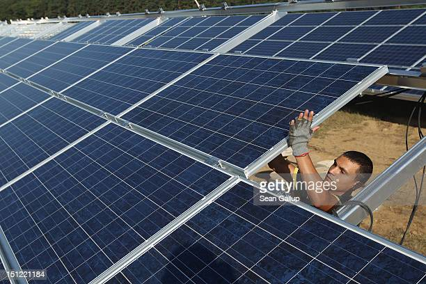 A worker installs solar panels containing photovoltaic cells at the new Solarpark Eggersdorf solar park on September 4 2012 near Muencheberg Germany...