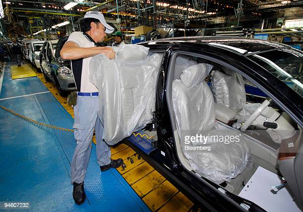 A worker installs the back seat into a Teana sedan on the production line of Nissan Motor Co's Siam Nissan factory some 20 kilometers east of Bangkok...