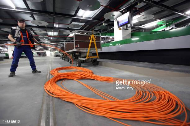 Worker installs wiring in the luggage loading area at Berlin Brandenburg Airport on May 4, 2012 in Schoenefeld, near Berlin, Germany. The new...