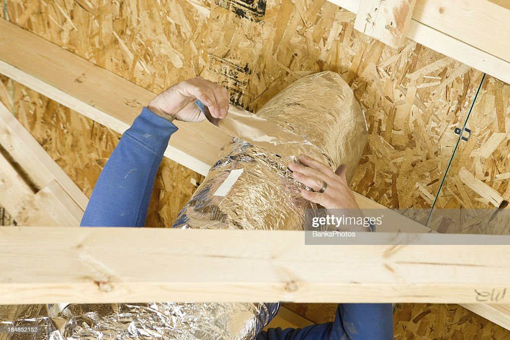 Worker Insulating an Attic Vent Duct with Aluminum Foil Tape : Stock Photo