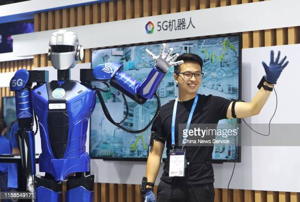 Worker interacts with a robot of robotics startup Roborn Dynamics Ltd on day one of the Mobile World Congress Shanghai 2019 at the Shanghai New...