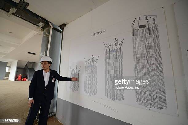 A worker introduces the building method of the 57floor Mini Sky City topped out in 19 days on March 17 2015 in Changsha China Local prefabricated...