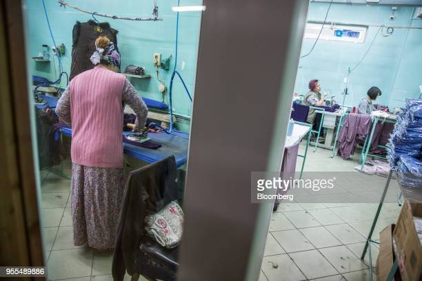 A worker irons clothing left as her colleagues operates sewing machines at an Alinex garment factory in Bishkek Kyrgyzstan on Wednesday April 18 2018...