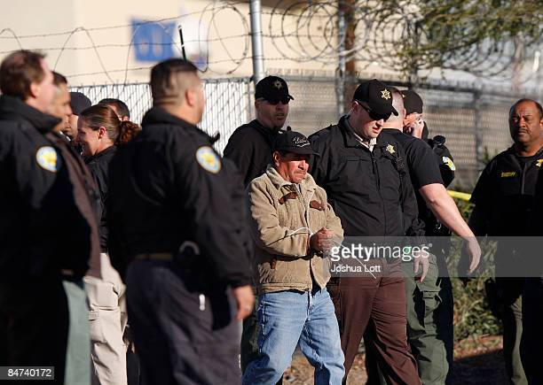 Worker is arrested as Maricopa County Sheriffs conduct an immigration raid at HMI Contracting February 11, 2009 in Phoenix, Arizona. Several...