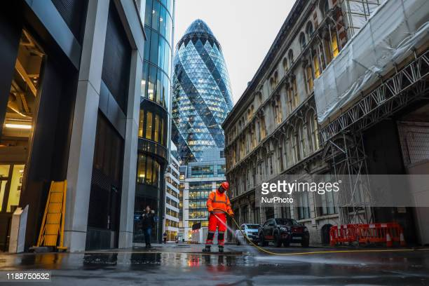 A worker is cleaning a street in The City area by 30 St Mary Axe in London United Kingdom on 11 December 2019