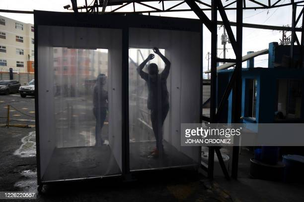A worker is disinfected in a chamber as he arrives for his shift at the textile plant KPTextil in San Miguel Petapa 20 km south of Guatemala City on...