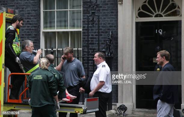 A worker is helped from 10 Downing Street the official residence of Britain's Prime Minister into an NHS ambulance by paramedics in central London on...