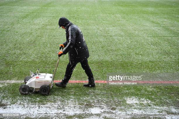 A worker is painting the sideline red due to snow fall prior to the Second Bundesliga match between FC Ingolstadt 04 and SG Dynamo Dresden at Audi...