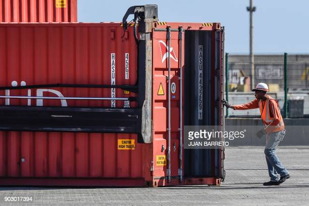 A worker is pictured at a container yard of the main port of 'La Guaira' in Caracas on January 9 2018 / AFP PHOTO / JUAN BARRETO