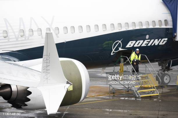 A worker is pictured next to a Boeing 737 MAX 9 airplane on the tarmac at the Boeing Renton Factory in Renton Washington on March 12 2019 US...
