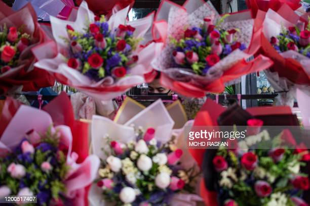 A worker is pictured through flowers for sale ahead of Valentine's Day in Kuala Lumpur on February 13 2020