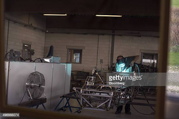A worker is reflected in a mirror as he welds the steel tubing of the chassis frame of a Donkervoort D8 GTO automobile at the Donkervoort...