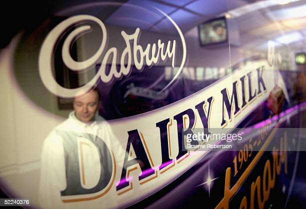 A worker is reflected in the Cadbury's chocolate logo at the entrance to the factory on February 25 2005 in Birmingham England The company is...