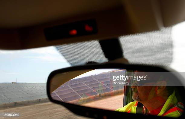 Worker is reflected in the rear view mirror while reviewing First Solar Inc. Photovoltaic solar panels at the Agua Caliente Solar Project in Yuma...