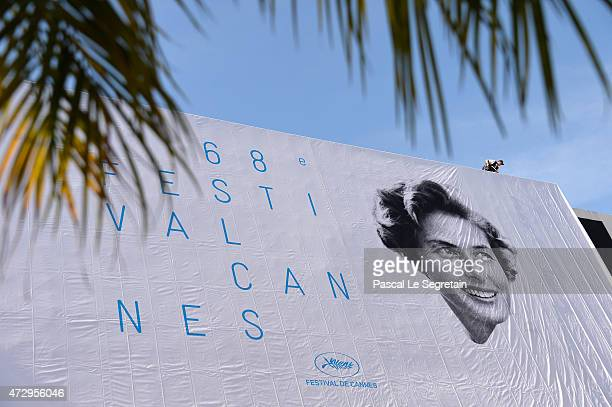 A worker is seen as he installs the official poster of the 68th Cannes Film Festival on the facade of the Palais des Festivals on May 11 2015 in...
