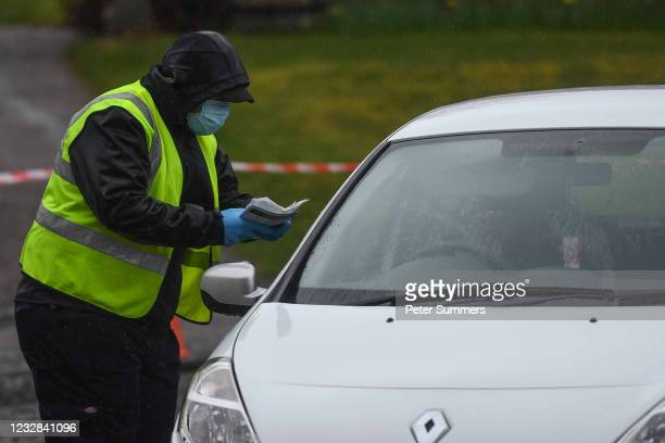 Worker is seen handing over a test kit at a mobile covid testing site on May 12, 2021 in Grantown-On-Spey, Scotland. NHS Highland has said the new...