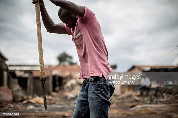 A worker is seen in Bitam in the north of Gabon near the border with Cameroon trying to clear the ground in the area of burnt warehouses on September...