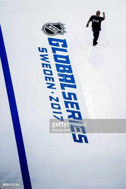 A worker is seen passing the Global Series logo during the rink build out ahead of the SAP NHL Global Series between Ottawa Senators and Colorado...