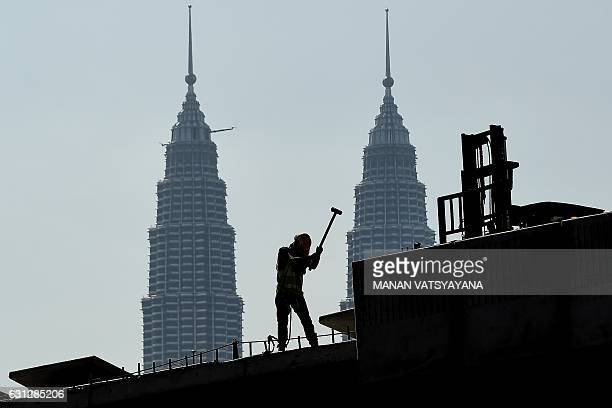 A worker is silhouetted against Malaysia's landmark Petronas Twin Towers as he works at an underconstruction site in Kuala Lumpur on January 9 2017 /...