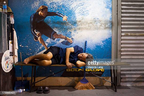 CONTENT] A worker is sleeping on a bench in a street with an advertising picture of a surfer behind him in George Town pulau Pinang Malaysia