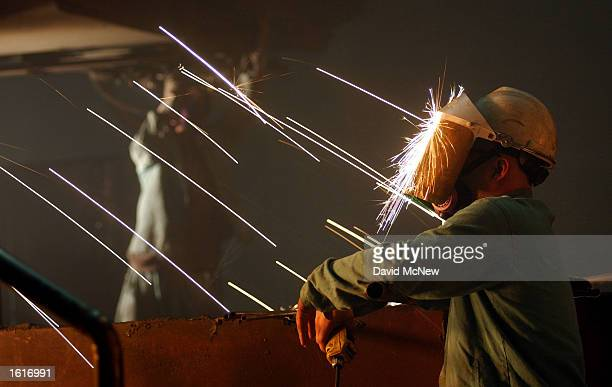 A worker is struck in the face with sparks from molten steel flowing into casts at the TAMCO steel mini mill on October 4 2002 in Rancho Cucamonga...