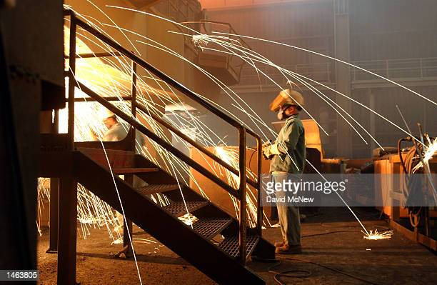 A worker is surrounded by sparks from molten steel flowing into casts at the TAMCO steel mini mill on October 4 2002 in Rancho Cucamonga California...