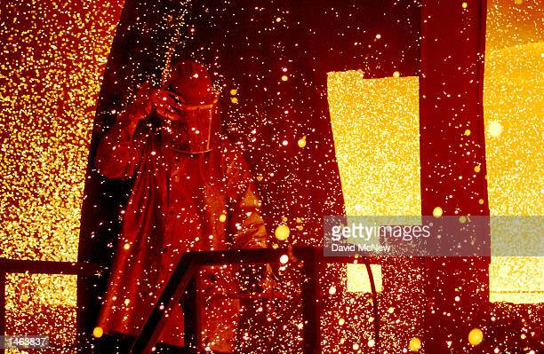 A worker is surrounded by splashes of molten steel at the TAMCO steel mini mill on October 4 2002 in Rancho Cucamonga California TAMCO California's...