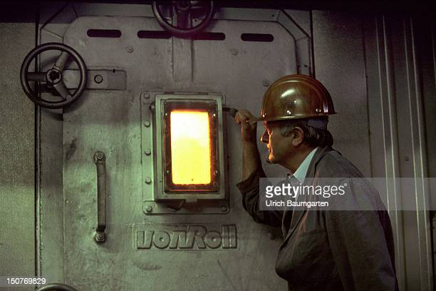 Worker is watching the fire inside an incinerator of an incinerating plant of the company TK environmental services
