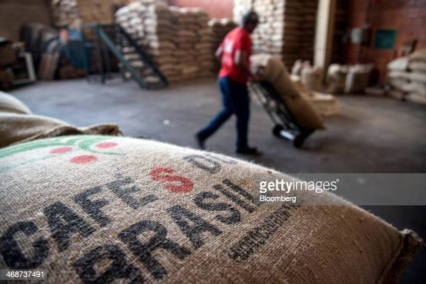 Worker Joao Avelar uses a hand cart to move bags of coffee beans that are going to be roasted at the Cafe Primavera facility in Itapira Brazil on...