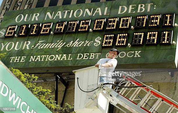 Worker John Abidelli mans a crane beneath the National Debt Clock after it was restarted July 11 2002 in New York City The digital sign shows the US...