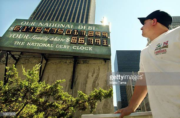 Worker John Abidelli stands beneath the National Debt Clock after it was restarted July 11 2002 in New York City The digital sign shows the US...