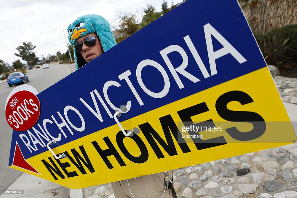 Worker Josh O'Neill spins a sign advertising new homes at the Rancho Victoria development in Rancho Cucamonga, California, U.S., on Sunday, Nov. 18, 2012. The U.S. Census Bureau is scheduled to release housing starts figures on Nov. 20. Photographer: Patrick T. Fallon/Bloomberg via Getty Images