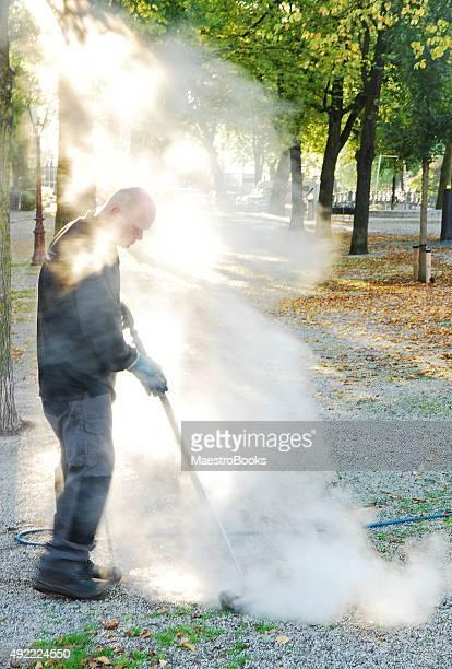 Arbeiter ums street Pflanzen mit warmen Wasser