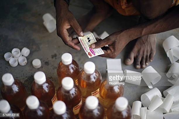 A worker labels a bottle of cow urine at a processing facility in Greater Noida Uttar Pradesh India on Friday June 17 2016 Urine from India's...
