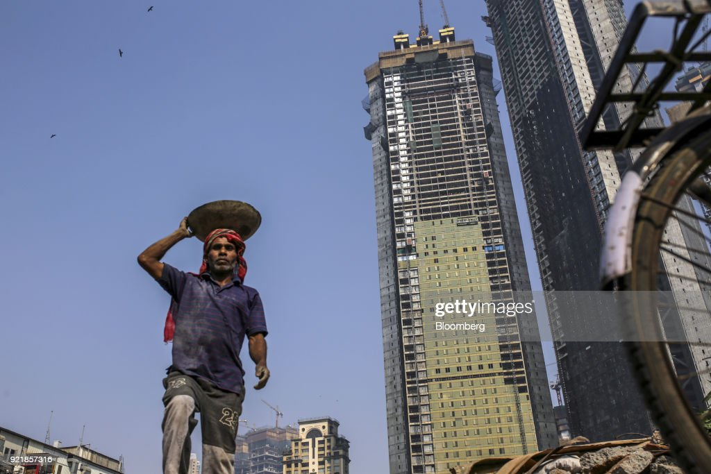 A worker labors as the two towers of Trump Tower Mumbai stand under construction at Lodha The Park, a luxury residential project developed by Lodha Developers Ltd., in Mumbai, India, on Tuesday, Feb. 20, 2018. India has the most construction projects with Trump licensing deals of any country outside of the U.S. Photographer: Dhiraj Singh/Bloomberg via Getty Images