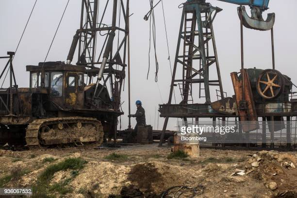 A worker labors at a pumpjack operating in Baku Azerbaijan on Sunday March 18 2018 Two years after descending into junk Azerbaijan's shortest path to...