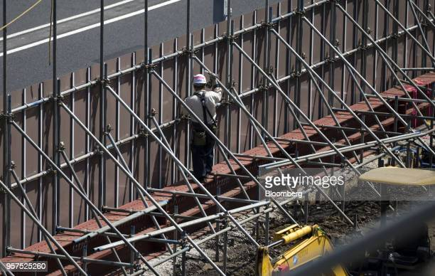 A worker labors at the construction site of the New National Stadium a venue for 2020 Summer Olympics and Paralympics in Tokyo Japan on Friday May 11...