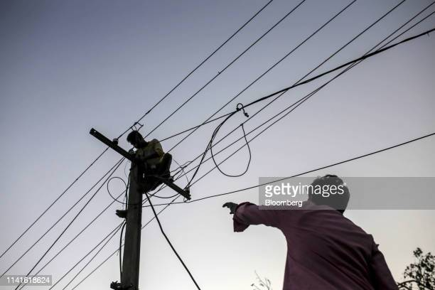 A worker labors atop an electricity pole in Bhubaneshwar Odisha India on Sunday May 5 2019 Authorities launched a massive restorationandrelief effort...
