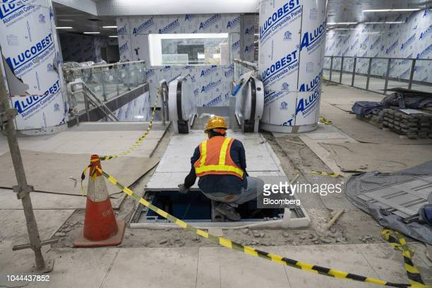 A worker labors in front of an escalator at the under construction Jakarta Mass Rapid Transit Bundaran Hi station in the Thamrin area of Jakarta...