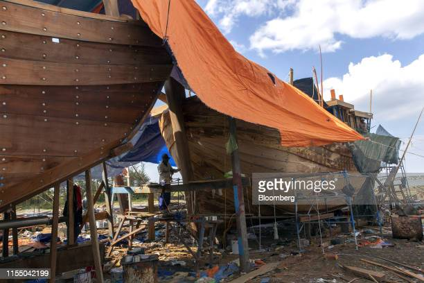 A worker labors on a fishing boat at a shipbuilding company in Quang Nam province Vietnam on Wednesday June 26 2019 Fishermen are on the front lines...