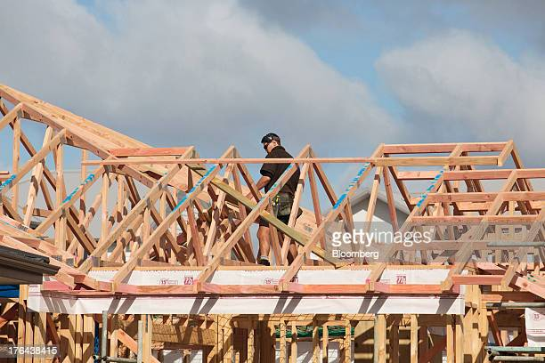 A worker labors on a house under construction in the suburb of Hobsonville Point in Auckland New Zealand on Tuesday Aug 13 2013 New Zealand's growth...
