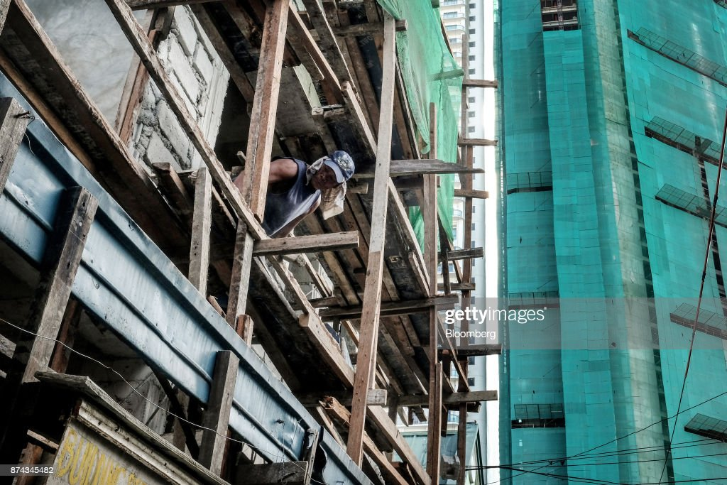 A worker labors on a ledge at a construction site in Mandaluyong, Metro Manila, Philippines, on Tuesday, Nov. 14, 2017. Economists are forecasting the Philippines to be among the first to raise interest rates in the region and the International Monetary Fund saidlast week the central bank should be ready to tighten if there are signs of overheating. Photographer: Veejay Villafranca/Bloomberg via Getty Images