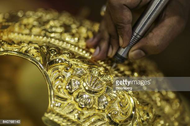 A worker labors on a six kilogram gold crown ahead of the Ganesh Chaturthi festival at a PN Gadgil Jewellers Pvt workshop in Pune India on Monday Aug...