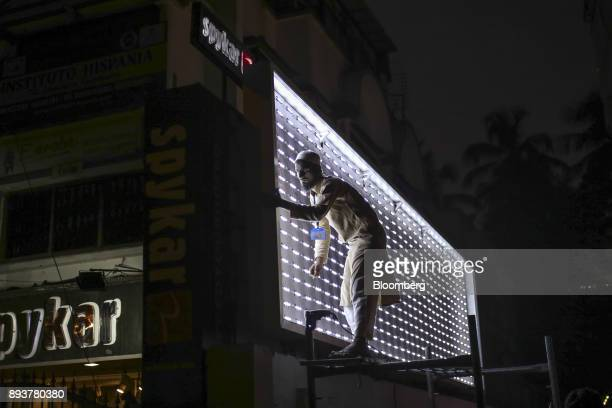 A worker labors on an illuminated billboard outside a store in Mumbai India on Friday Dec 15 2017 India's inflation surged past the central bank's...