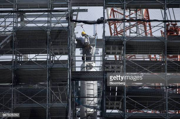 A worker labors on scaffolding at the construction site of the New National Stadium a venue for 2020 Summer Olympics and Paralympics in Tokyo Japan...