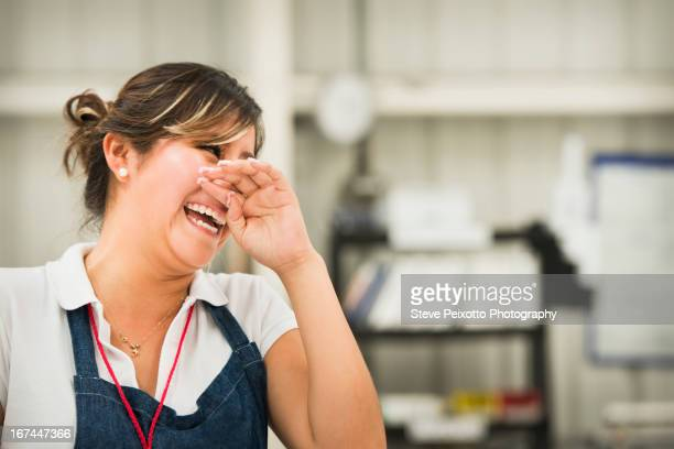 Worker laughing in manufacturing plant